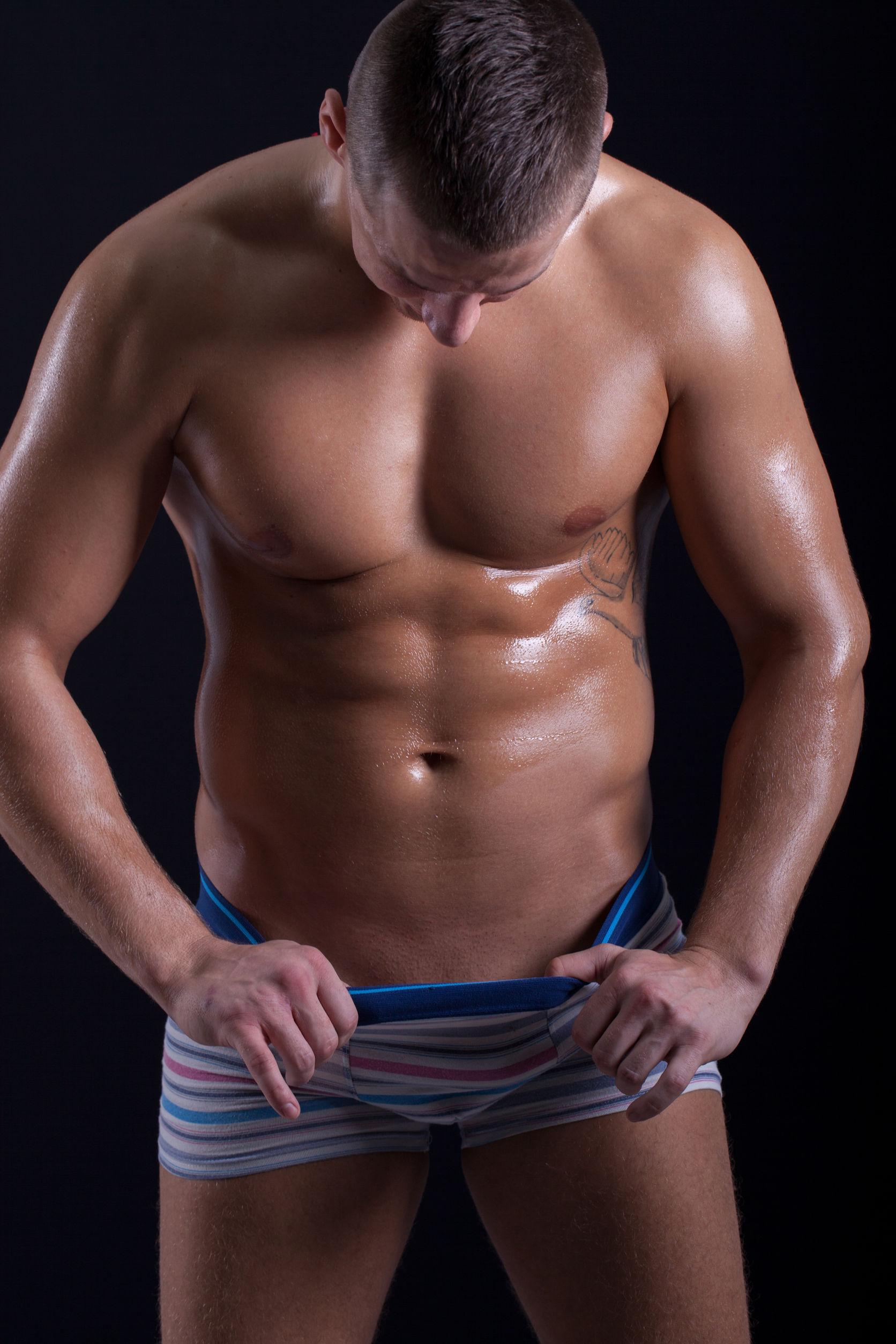 28703523 - muscular  man looking down in his pants
